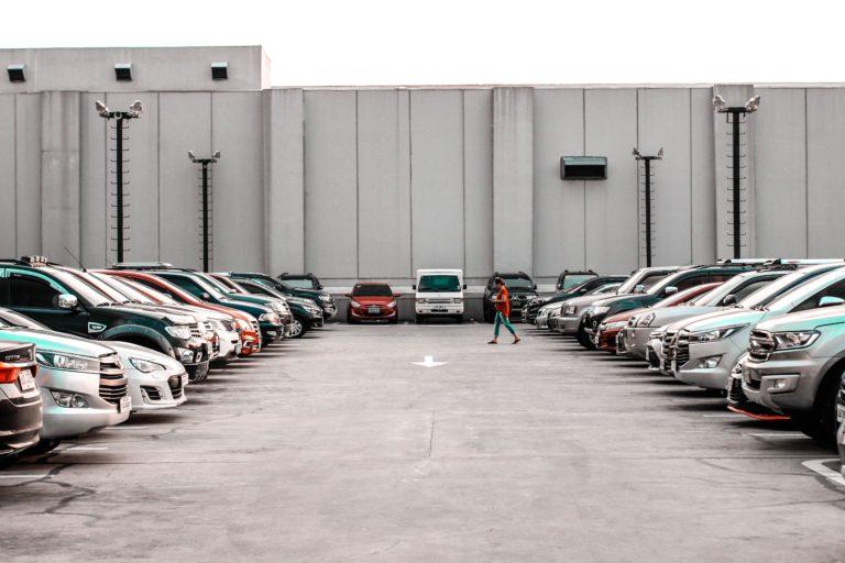 A woman is walking through a full car park.